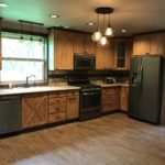 Open kitchen with fridge, gas stove, dishwasher and custom cabinets.